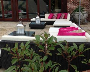 black rattan with cream covers and hot pink scatters: furniture hire hertfordshire