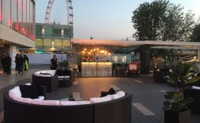 rattan furniture on south bank with london eye in the background