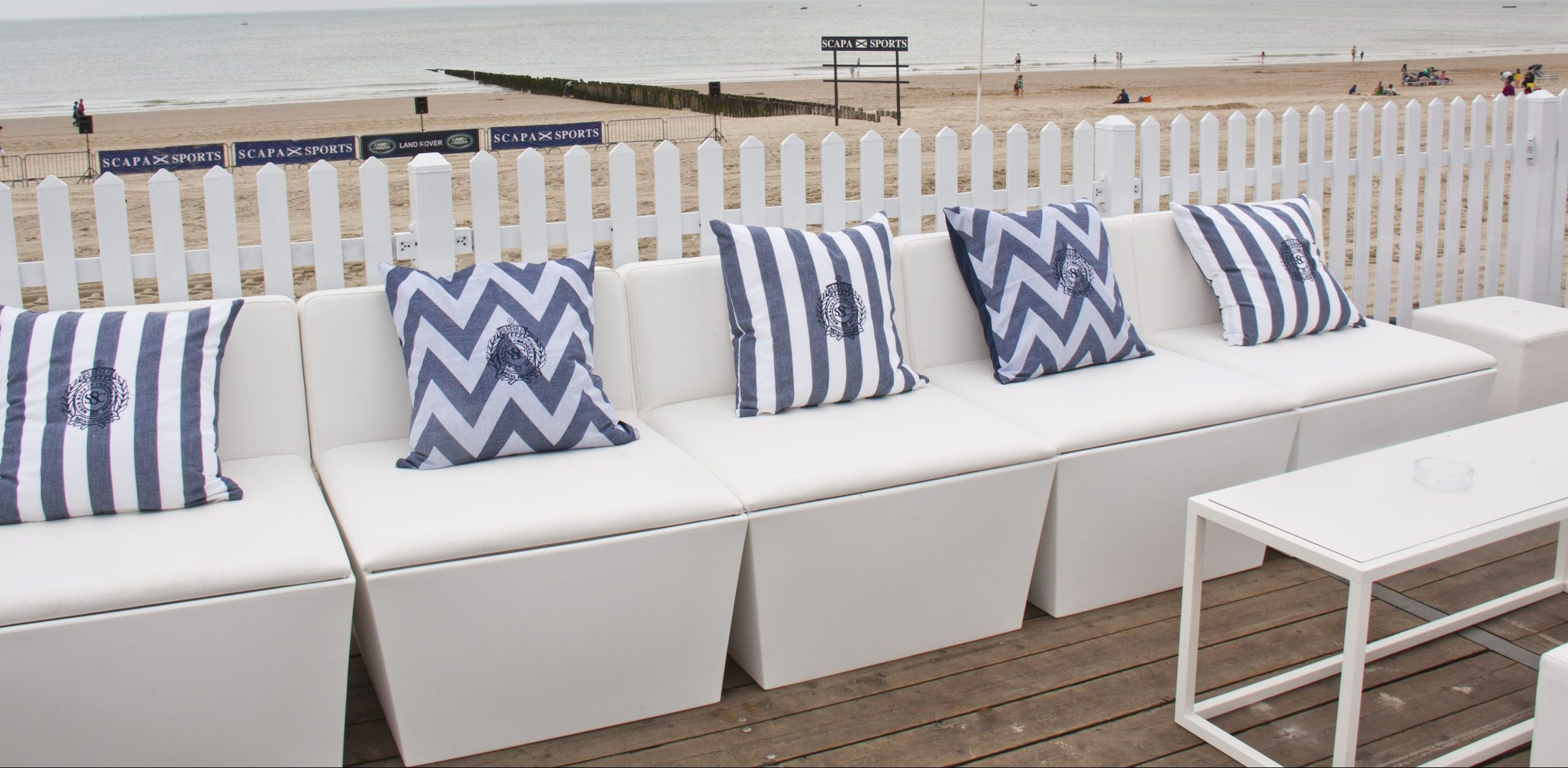 funky furniture hire: white modular sofas with stripe cushions