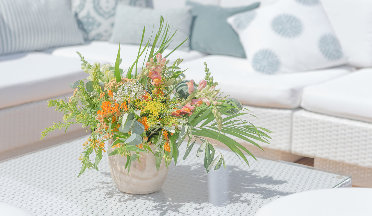 chill out furniture hire: white rattan sofas with flowers