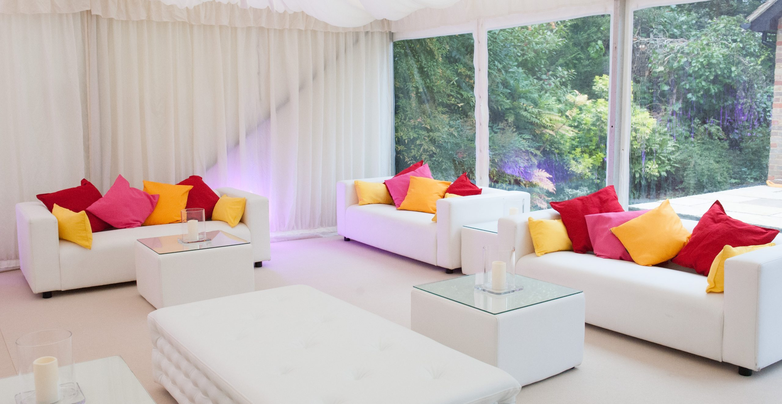 marquee furniture hire: chesterfield benches and white sofas bright cushions
